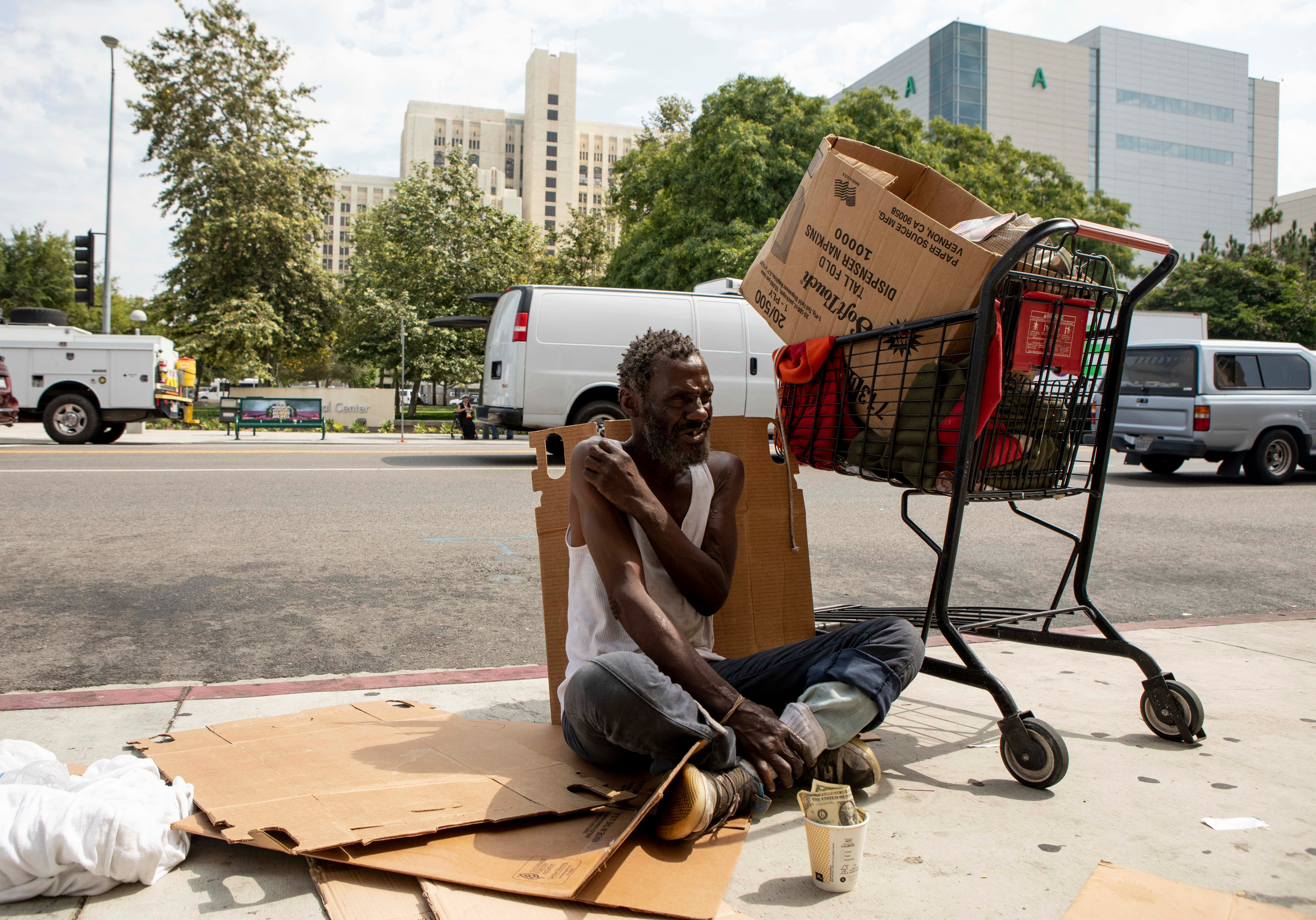 Will, who provided his first name only, sits on the sidewalk in Los Angeles. Will has been homeless since he arrived in Los Angeles in 1982. Photo by Anne Wernikoff for CalMatters